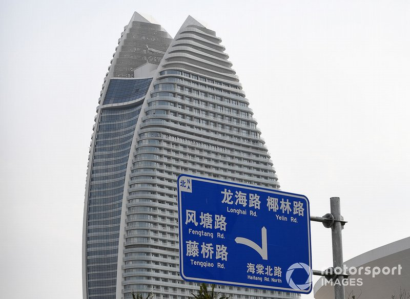A road sign, a skyscraper in the background