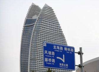 A road sign, a skyscraper in the background