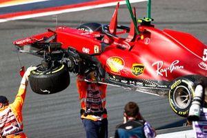 Los oficiales de pista retiran el coche dañado de Carlos Sainz Jr., Ferrari SF21