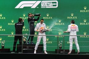 The Mercedes trophy delegate, Valtteri Bottas, Mercedes, 1st position, Max Verstappen, Red Bull Racing, 2nd position, and Sergio Perez, Red Bull Racing, 3rd position, celebrate with Champagne on the podium