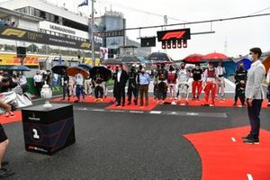 The drivers stand for the national anthem prior to the start