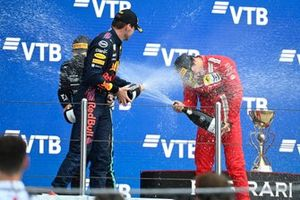 Max Verstappen, Red Bull Racing, 2nd position, and Carlos Sainz Jr., Ferrari, 3rd position, spray Champagne on the podium