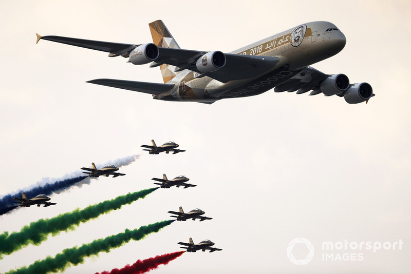 UAE display team Al Fursan escort an Airbus A380 of Etihad Airlines over the grid in their Aermacchi MB339A aircraft