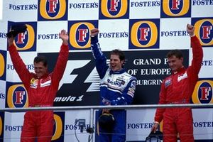Podium: tweede Michael Schumacher, Ferrari, winnaar Jacques Villeneuve, Williams, derde David Coulthard, McLaren