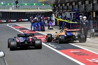 Alexander Albon, Toro Rosso STR14, y Lando Norris, McLaren MCL34, corren para ser los primeros en salir de los pits