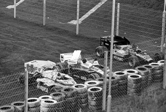 The Arrows A7 of Marc Surer, the Toleman TG184 of Ayrton Senna, and the ATS D7 of Gerhard Berger are parked by the tyre barrier at the end of the main straight after a multi-car collision on the opening lap of the race