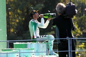 Pierre Gasly, AlphaTauri, 1st position, sits on the podium and drinks some Champagne