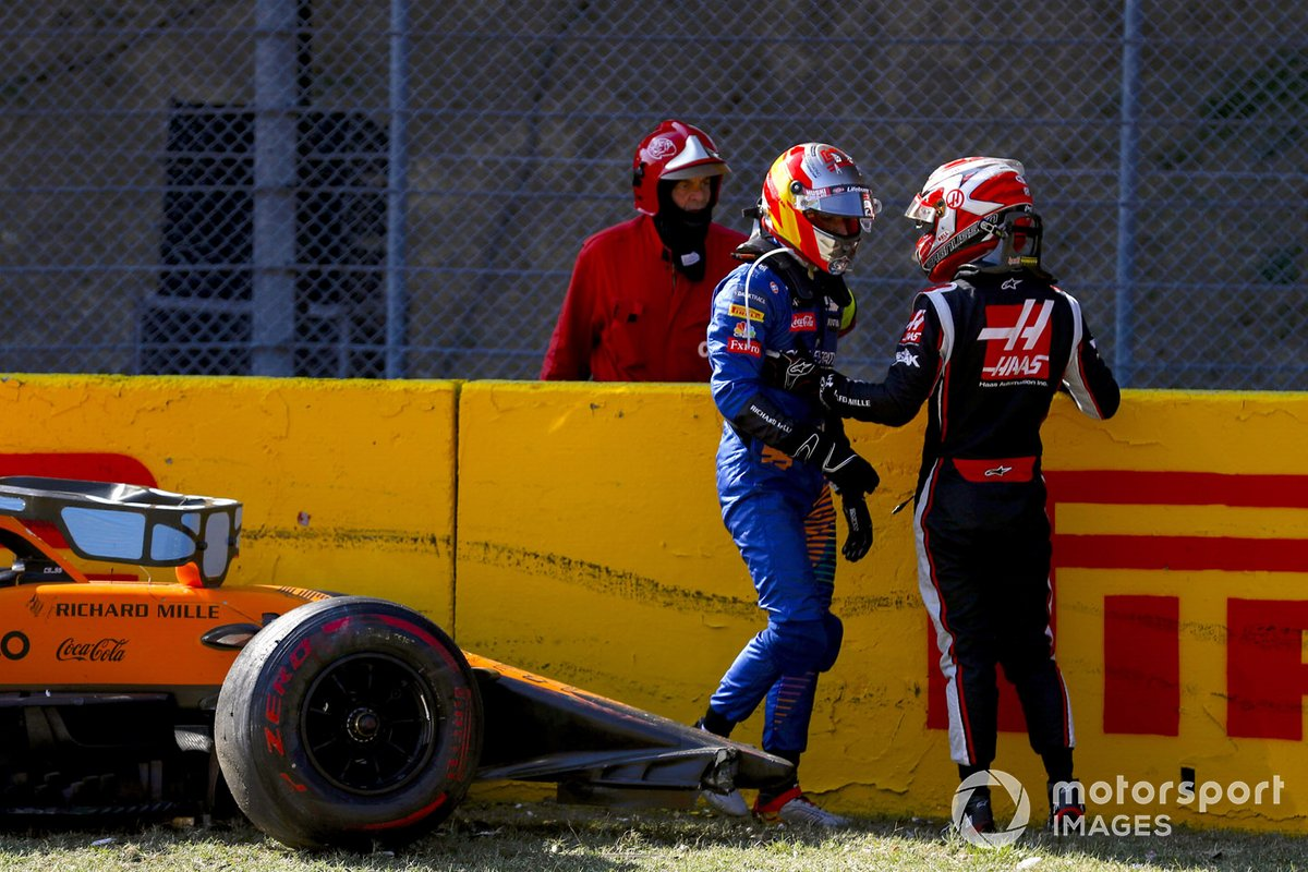 Carlos Sainz Jr., McLaren, and Kevin Magnussen, Haas F1, talk after crashing out of the race