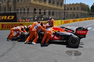 Marshals move the damaged car of Max Verstappen, Red Bull Racing RB16B