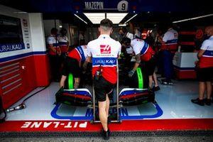 Haas F1 mechanics work on the car of Nikita Mazepin, Haas VF-21, in the garage