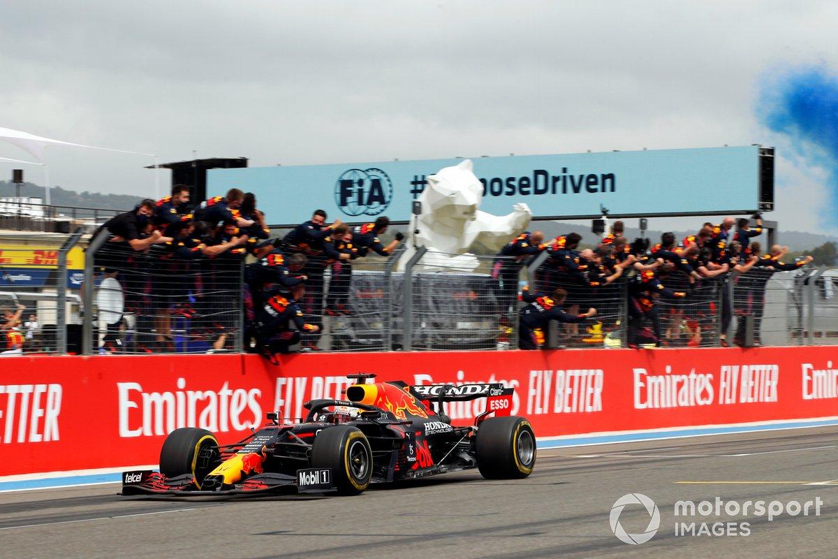 Max Verstappen, Red Bull Racing RB16B, 1ª posición, cruza la línea de meta para la victoria entre los vítores de su equipo en el muro de boxes