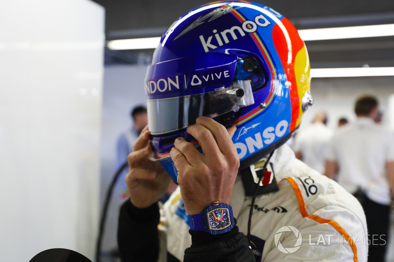 Fernando Alonso, McLaren, adjusts his helmet