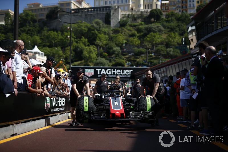 Une Haas VF-18 poussée par des mécaniciens Haas F1