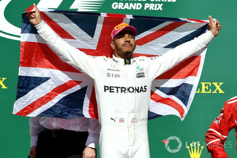 Race winner Lewis Hamilton, Mercedes AMG F1 celebrates on the podium with the Union Jack flag