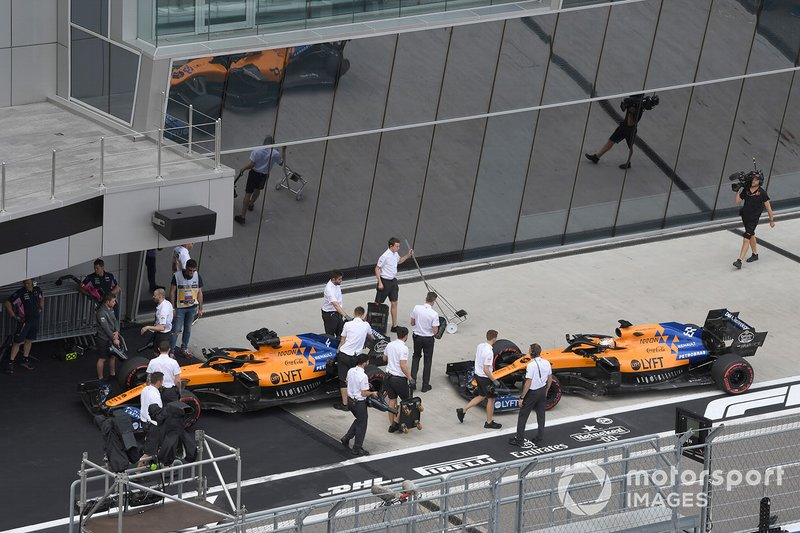 the cars of Lando Norris, McLaren MCL34, and Carlos Sainz Jr., McLaren MCL34, in the pit lane