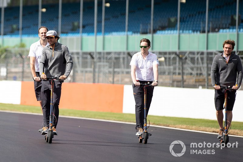 Carlos Sainz Jr., McLaren walks the track on a scooter