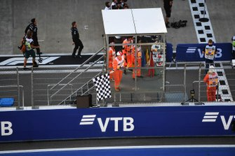 A Marshal waves the chequered flag