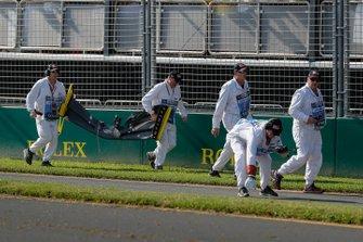 Oficiales remueven el alerón delantero y los escombros pertenecientes al coche de Daniel Ricciardo, Renault, del circuito