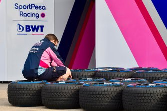 A Racing Point mechanic at work sorting through tyres