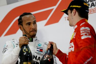 Lewis Hamilton, Mercedes AMG F1, 1st position, and Charles Leclerc, Ferrari, 3rd position, click Champagne bottles on the podium