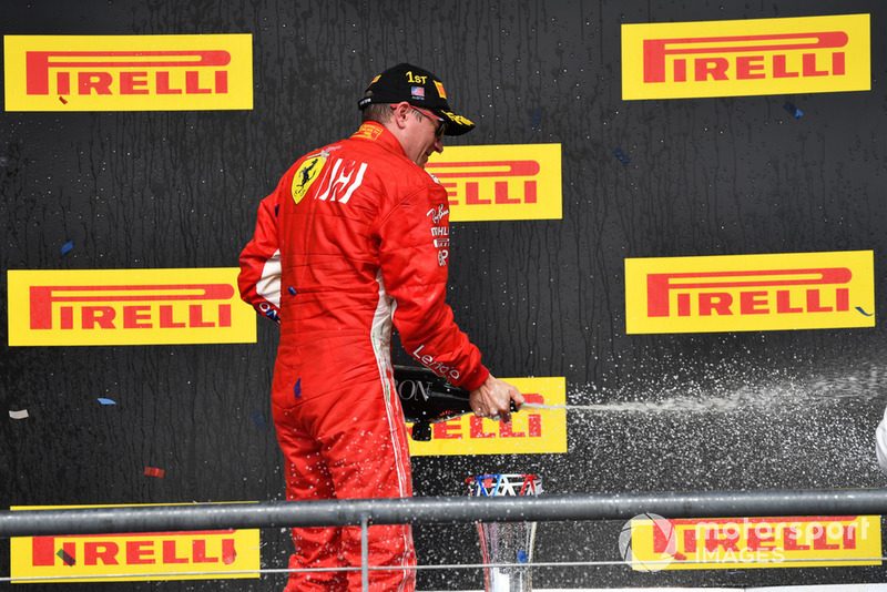 Race Winner Kimi Raikkonen, Ferrari celebrates with the champagne on the podium with the trophy