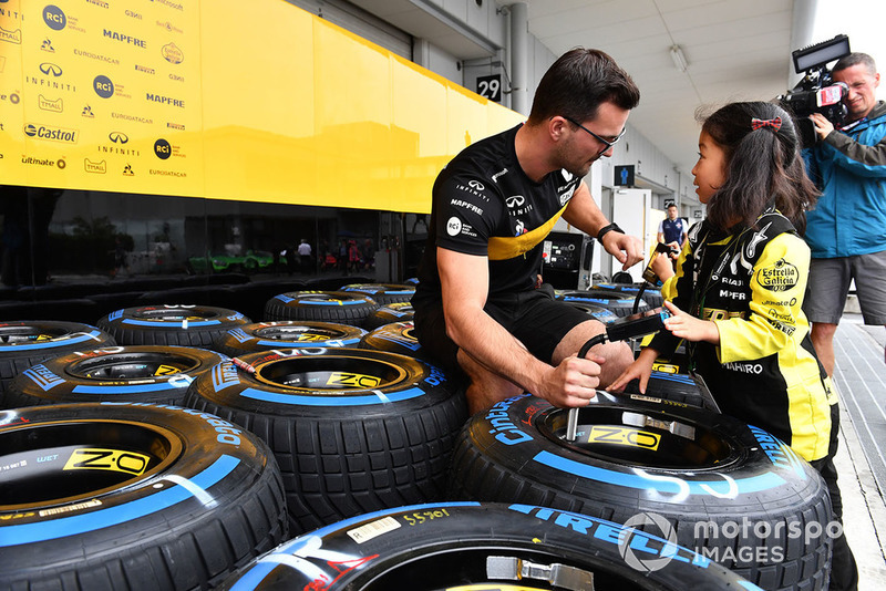 Renault Sport F1 Team mechanic with Pirelli tyres and young fans