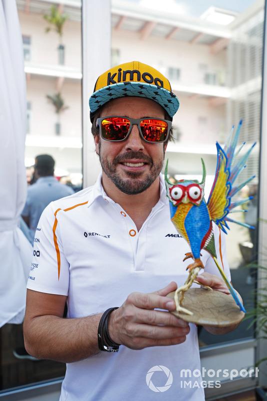 Fernando Alonso, McLaren, holds an Alebrijes sculpture