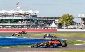 Lando Norris, McLaren MCL35M, Fernando Alonso, Alpine A521, and Daniel Ricciardo, McLaren MCL35M