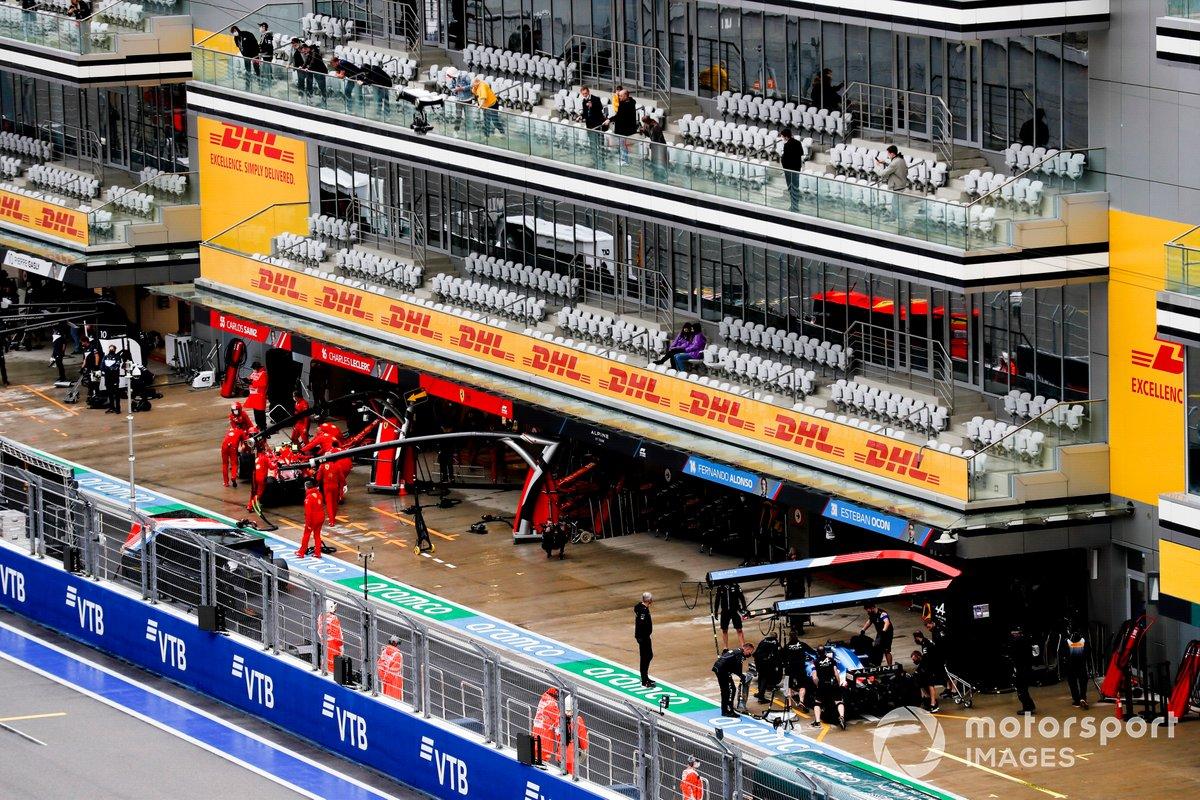 Carlos Sainz Jr., Ferrari SF21, y Fernando Alonso, Alpine A521, en el pit lane