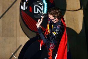 Max Verstappen, Red Bull Racing, 1e plaats, viert feest op het podium terwijl hij een cape met Nederlandse vlag draagt