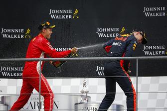 Sebastian Vettel, Ferrari, 1st position, blasts Max Verstappen, Red Bull Racing, 3rd position, with Champagne on the podium
