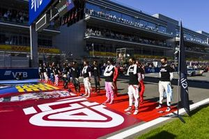 The drivers stand on the grid