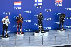 Russian politician Dimitry Kozak, the Mercedes trophy delegate, Max Verstappen, Red Bull Racing, 2nd position, Valtteri Bottas, Mercedes-AMG F1, 1st position, and Lewis Hamilton, Mercedes-AMG F1, 3rd position, on the podium