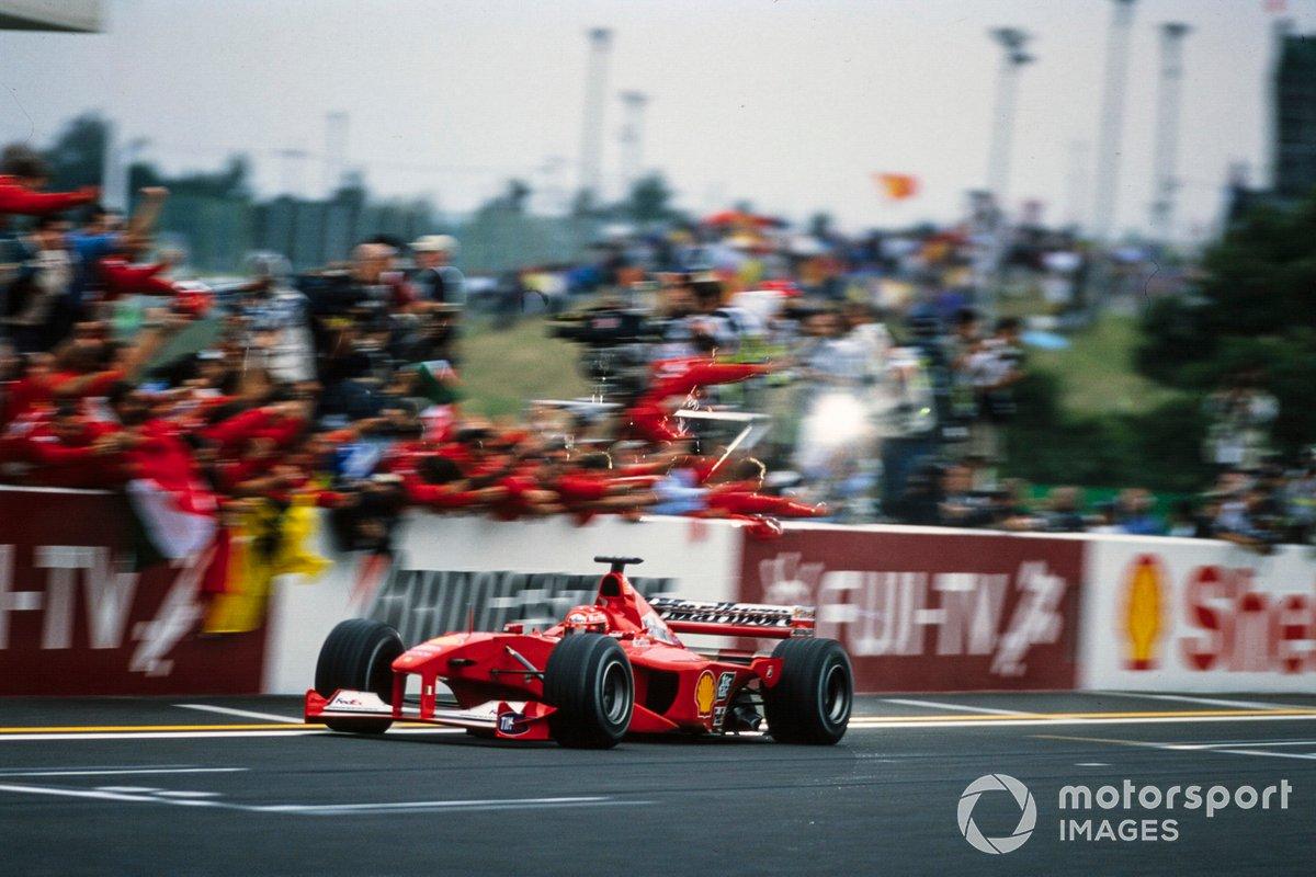 Michael Schumacher, Ferrari F1-2000, cruza la línea de la victoria en la carrera y el campeonato mundial de pilotos