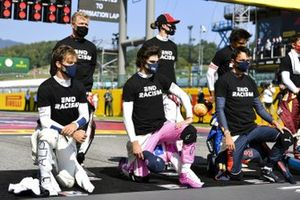 Pierre Gasly, AlphaTauri, Lance Stroll, Racing Point, Alex Albon, Red Bull Racing, and the other drivers kneel and stand in support of the End Racism campaign prior to the start