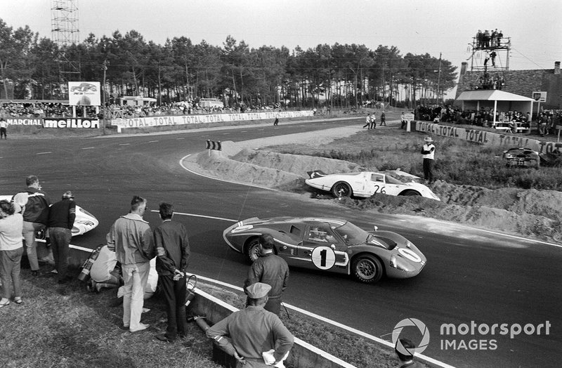 Dan Gurney, A.J. Foyt, Shelby-American, Ford GT40 Mk.IV, passes the crashed car of Chuck Parsons, Ricardo Rodriguez-Cazados, North American Racing Team, Ferrari 365P2