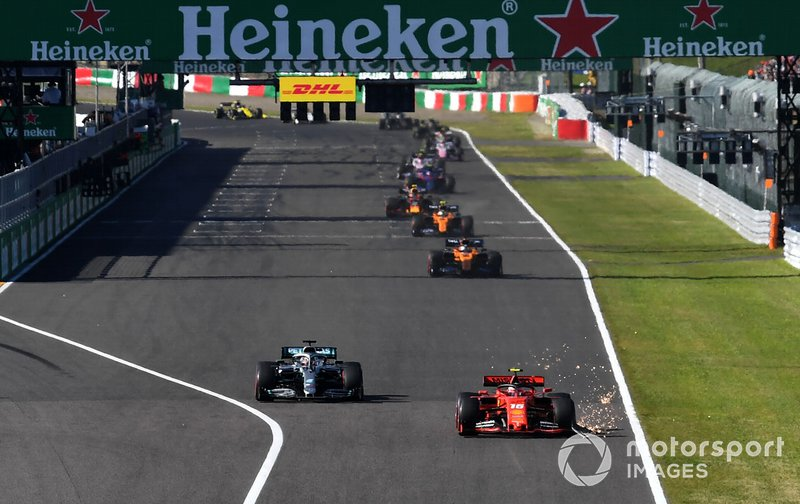 Charles Leclerc, Ferrari SF90,leads Lewis Hamilton, Mercedes AMG F1 W10, a sparks trail from his broken front wing
