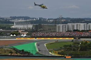 An Helibrás AS-350B3 Esquilo (license built Eurocopter AS-350 Squirrel) camera helicopter in the same colours as the helmet of Ayrton Senna flies over as the cars head around the formation lap