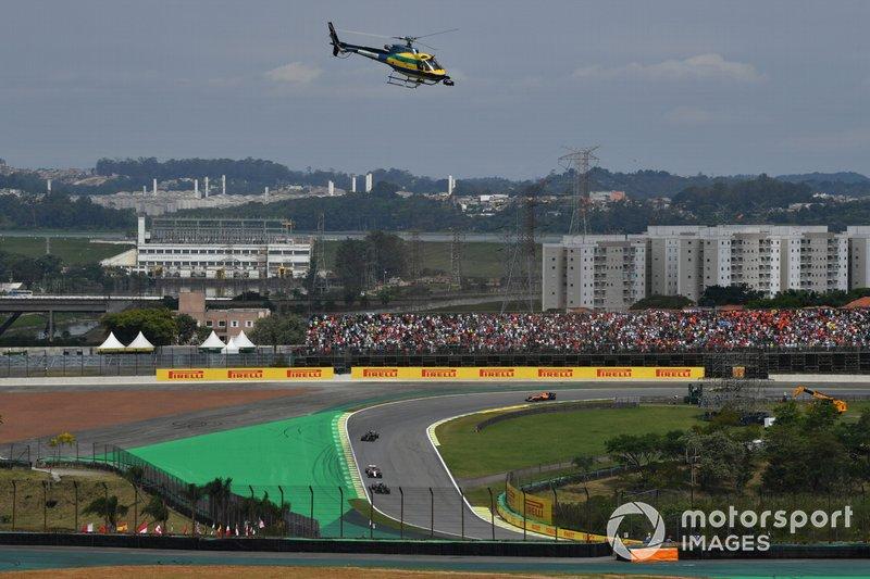 Helicóptero de cámara con los mismos colores que el casco de Ayrton Senna, mientras los coches se dirigen alrededor de la vuelta de formación.