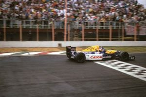 Nigel Mansell, Williams FW14B Renault, raises his arm as he crosses the line