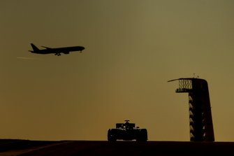 Un avion de ligne dans le ciel alors qu'une monoplace est en piste à Austin