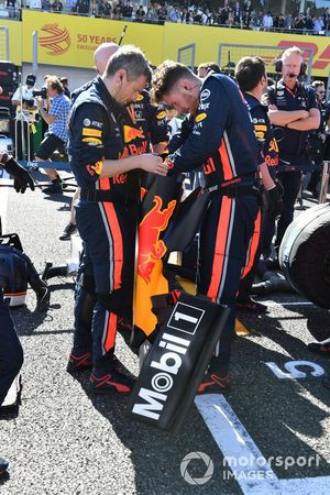 Red Bull mechanics look at a front wing set up on the grid