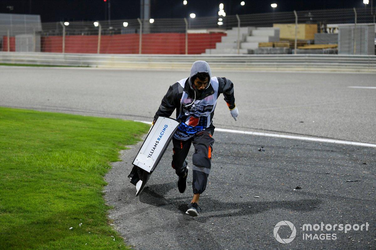 Un oficial retira el ala de Jack Aitken, Williams FW43, del circuito