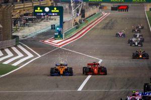 Lando Norris, McLaren MCL35, battles with Sebastian Vettel, Ferrari SF1000, as sparks fly