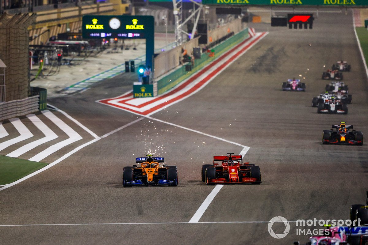 Lando Norris, McLaren MCL35, battles with Sebastian Vettel, Ferrari SF1000, as sparks fly