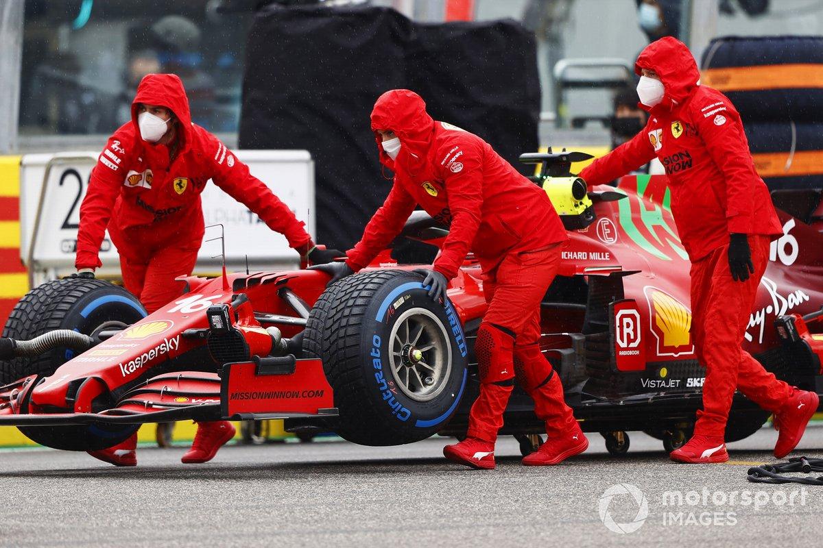 I meccanici muovono l'auto di Charles Leclerc, Ferrari SF21, sulla griglia di partenza