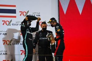 Lewis Hamilton, Mercedes-AMG F1, 1st position, Alex Albon, Red Bull Racing, 3rd position, and the Mercedes trophy delegate celebrate on the podium with Champagne