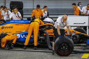 Un mecánico quita una rueda del McLaren MCL35 de Carlos Sainz, mientras que otros trabajan en el coche que está detrás de él