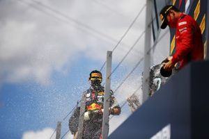 Max Verstappen, Red Bull Racing, 2nd position, Lewis Hamilton, Mercedes-AMG F1, 1st position, and Charles Leclerc, Ferrari, 3rd position, spray Champagne on the podium