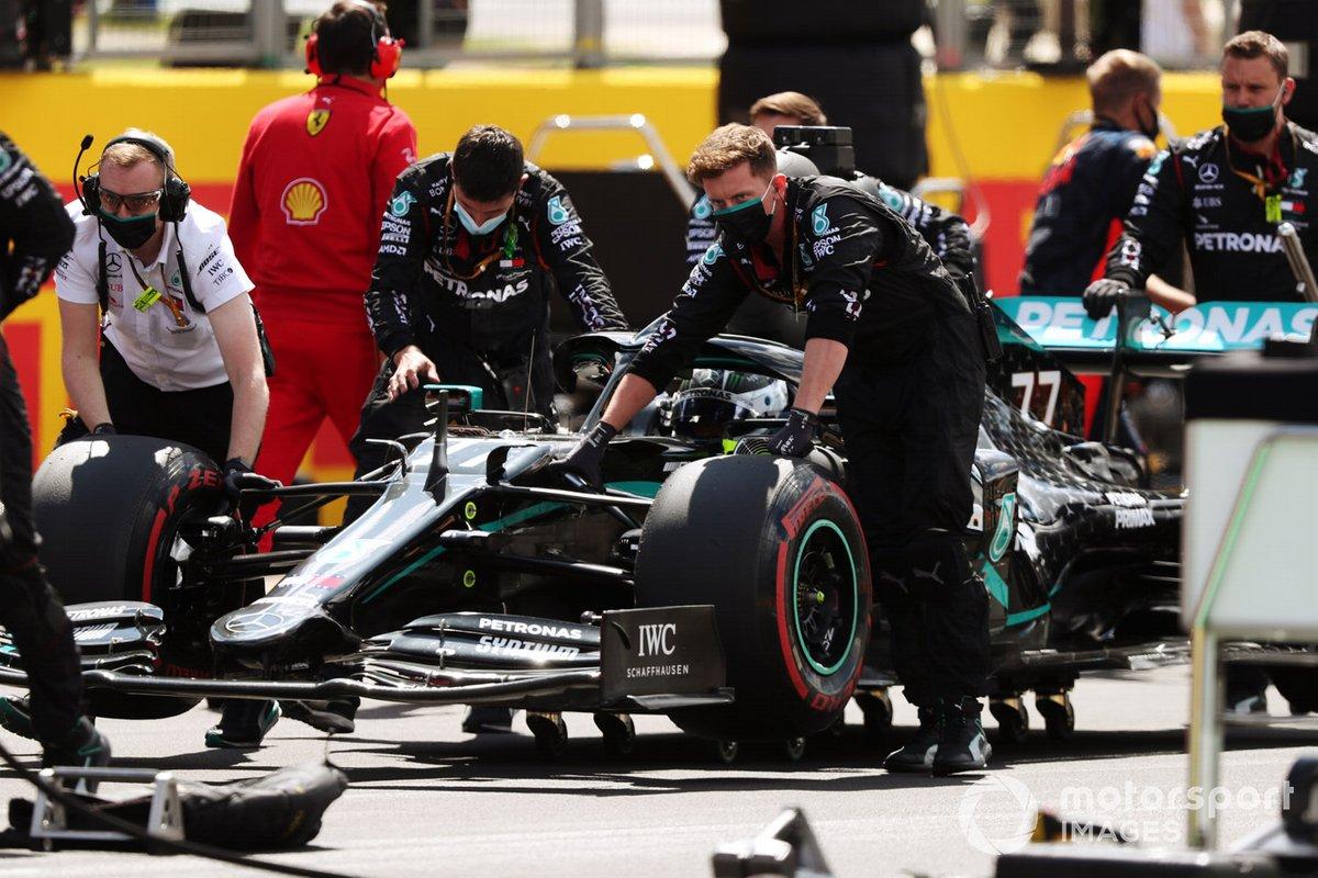 Los mecánicos posicionan a Valtteri Bottas, Mercedes F1 W11, en su lugar en la parrilla
